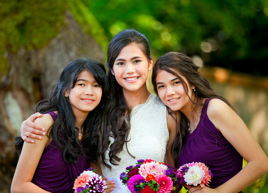 Biracial bride standing with her two bridesmaids outside smiling and holding flower bouquet