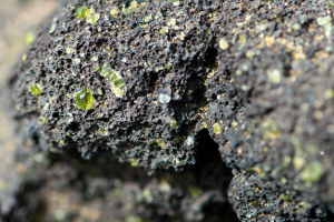 Close up view of lava rock with green olivine.