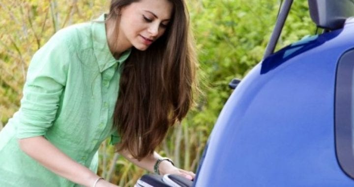 young-woman-putting-suitcase-in-blue-car_iStock-384821367