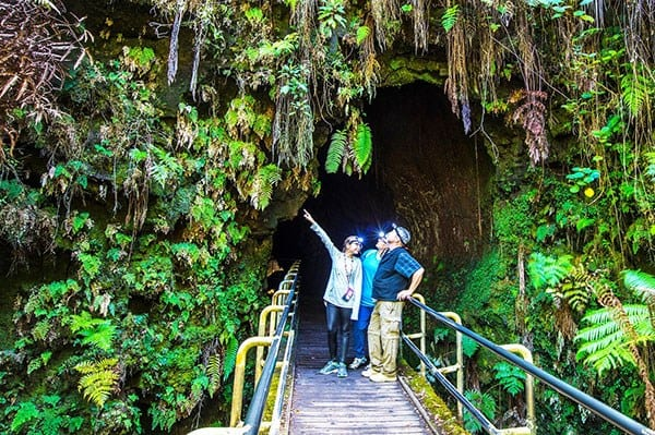 Visitors stand outside of the entrance to Nahuku lava tube.