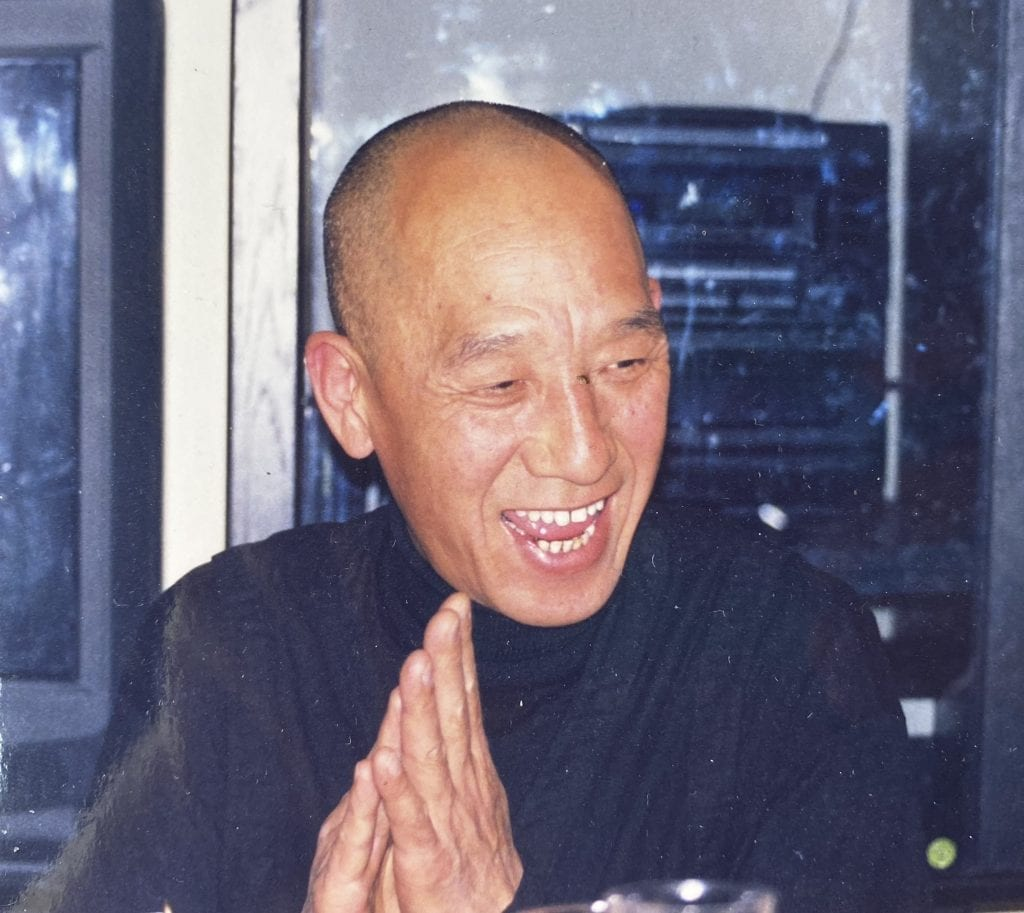 Shingo Honda laughing with hands in prayer