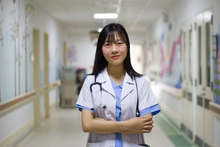 a doctor stands in a hospital with her arms crossed