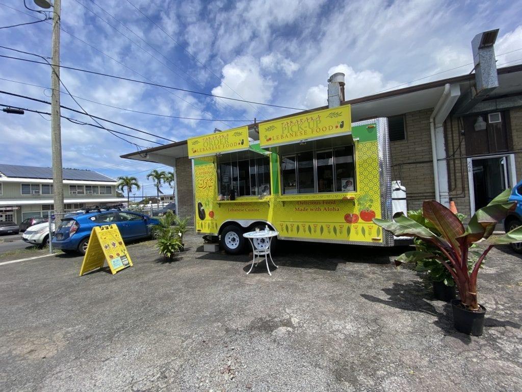 Tabaraka's yellow food trailer under a cloud-filled blues sky
