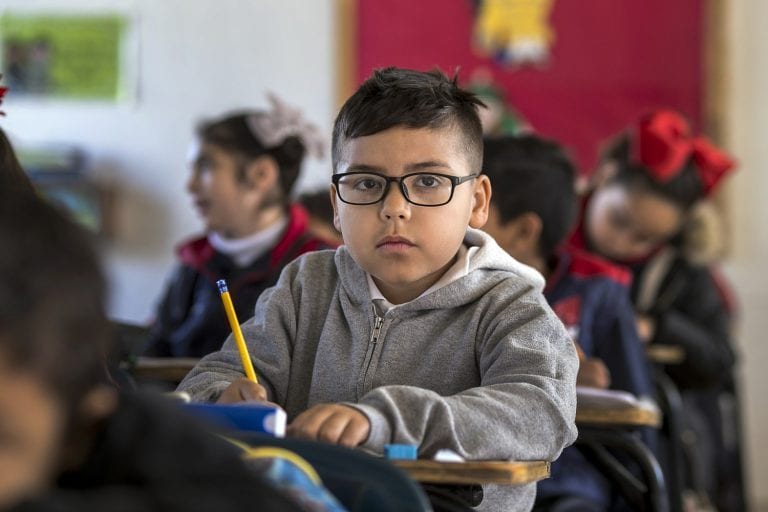 a young boy sits in a classroom