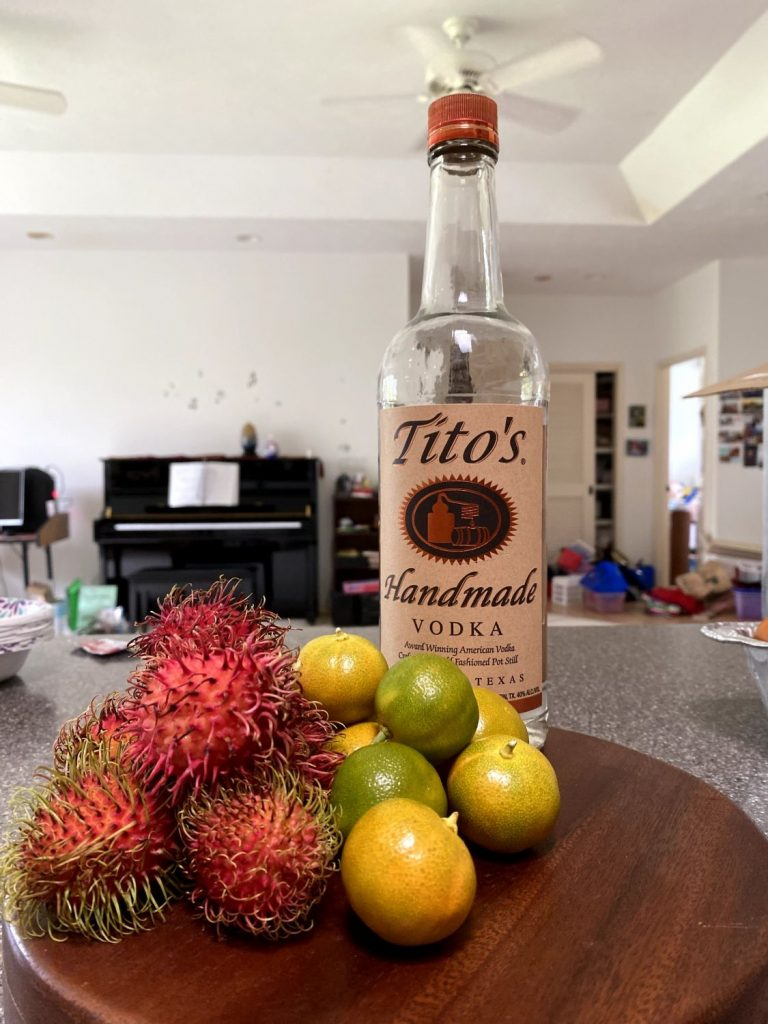 a bottle of Tito's, calamansi limes, and rambutan for a Living Hilo Style cocktail