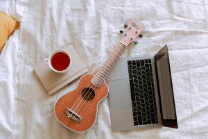 an ukulele, laptop, and tea sit on awhite bed
