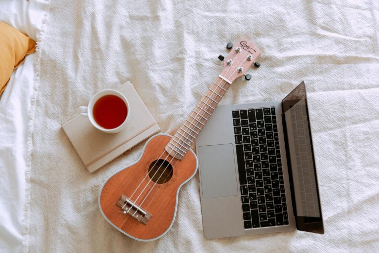 an ukulele, laptop, and tea sit on awhite bed