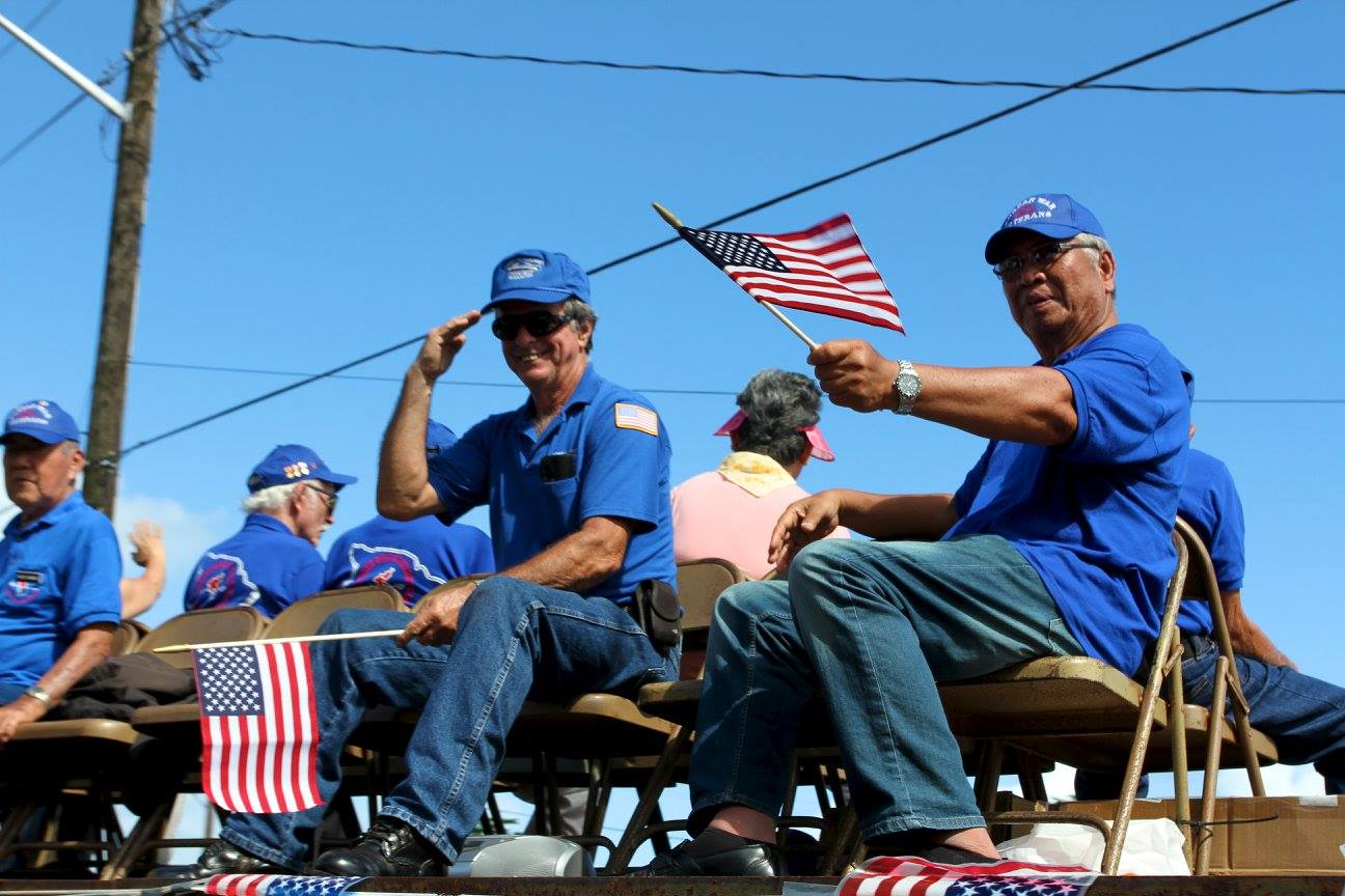 Veterans wave flags from a parade float during Hawaii Island Veterans Day Parade
