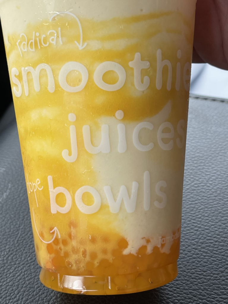a clear cup from Jamba Hawaii is filled with orange and white liquid and orange boba spheres