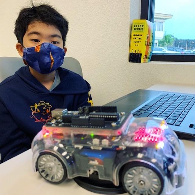 a child wears a mask while sitting in front of a laptop for a Hawaii Technology Academy class