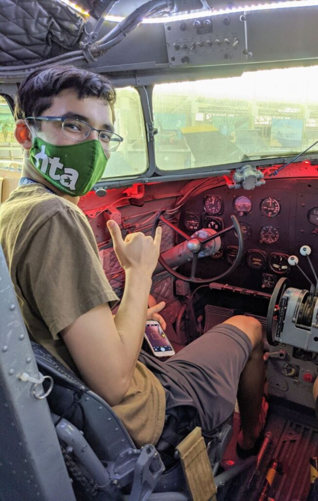 A masked student sits in the cockpit of a plane during a Hawaii Technology Academy learning event