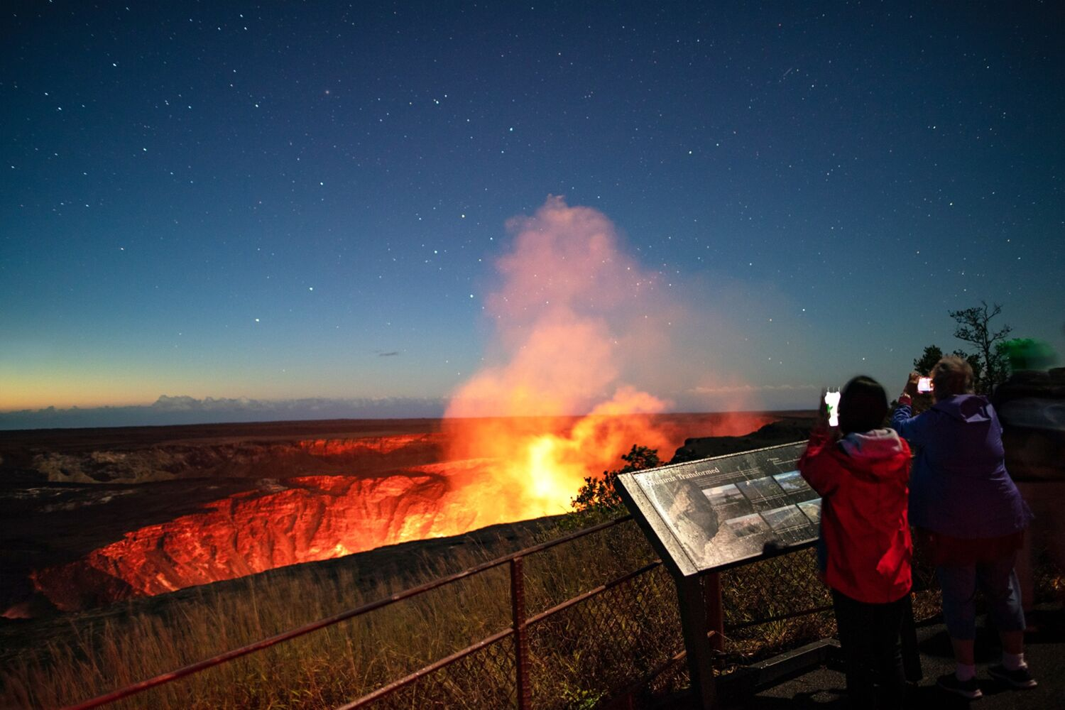 Two adults watch the glow from lava at Hawaii Volcanoes National Park.