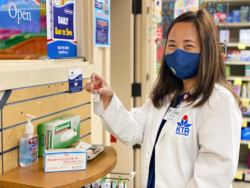 A KTA Pharmacy employee holds a Covid vaccine